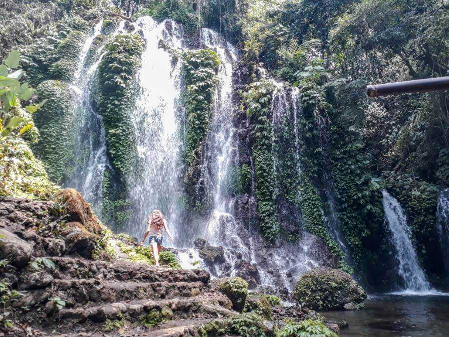 Girl walking towards waterfall at Banyu Wana Amertha Waterfalls