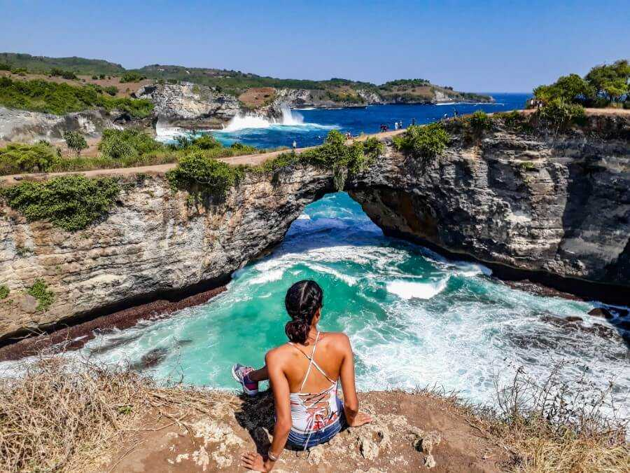 Girl sitting on top of cliffs at the Broken Beach in Nusa Penida