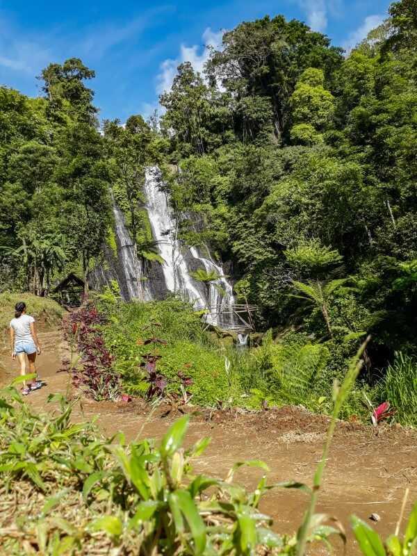 Girl walking towards Banyumala Twin Waterfalls