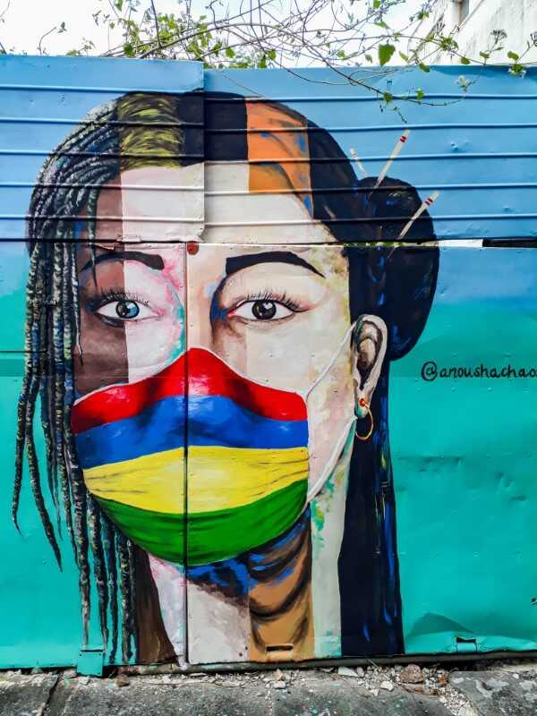 Street art of woman wearing a mask in the colors of the Mauritian flag