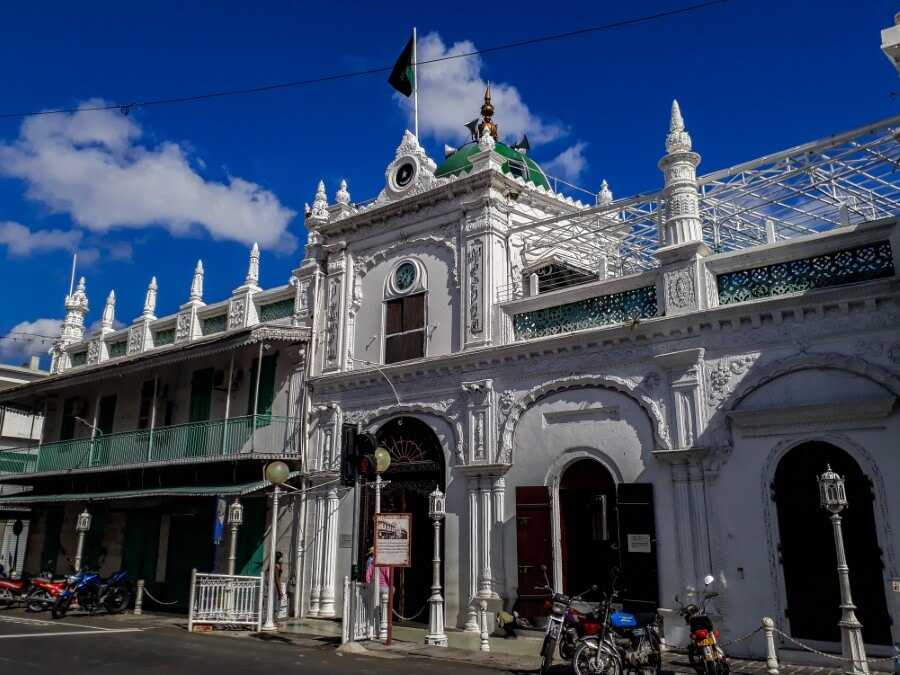 A white mosque with green accents