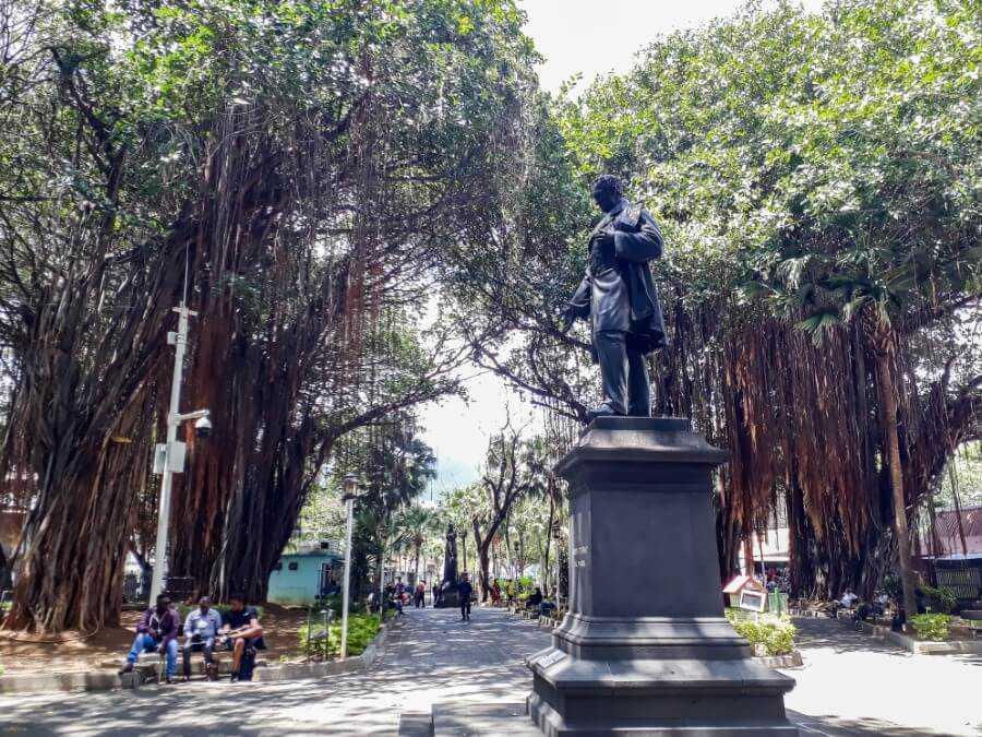 Statue and tall banyan trees at Les Jardins de la Compagnie