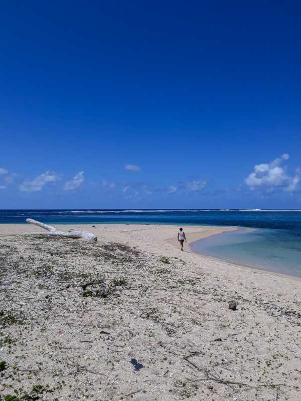 Girl walking on a white sand beach in the south of Mauritius