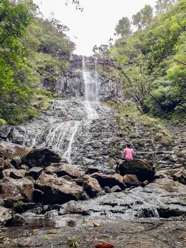 girl looking at waterfall cascading down a steep cliff at Alexandra Falls