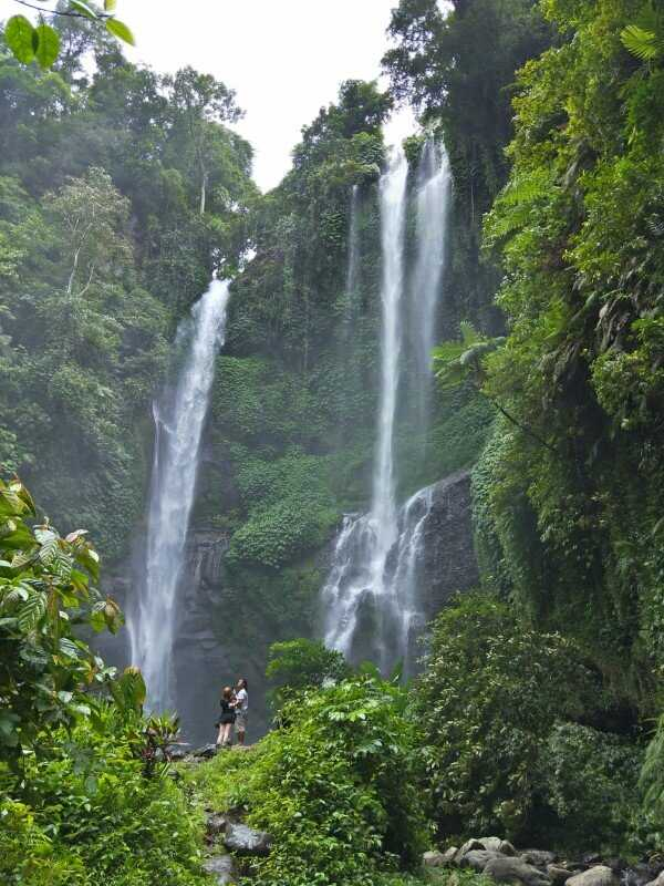 two people standing in front to sekumpul waterfall