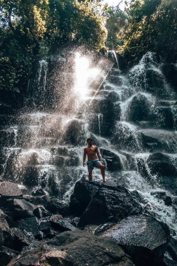 Man standing in front of Kanto Lampo Waterfall in Ubud