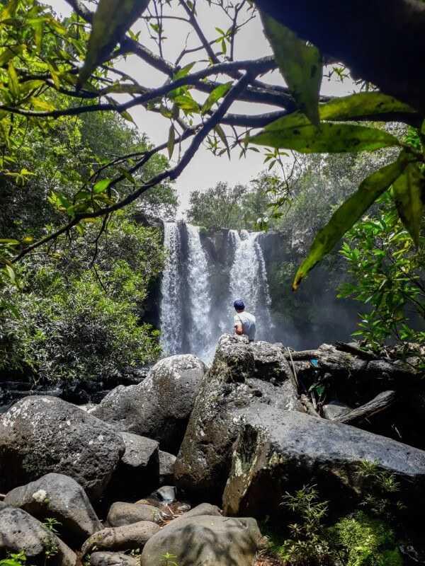 man sitting on a boulder watching Exil waterfall